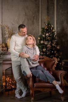 Взрослая красивая женщина и мужчина сидят на диване возле елки