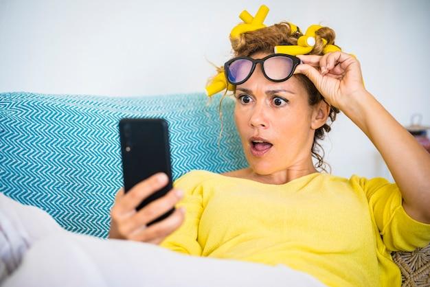大人の美女が自宅の携帯電話を見て驚きます