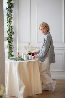 흰색 식탁보와 둥근 축제 테이블을 제공하는 성인 아름다운 여자