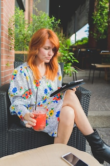 Adult beautiful woman sitting outdoor having drink using tablet