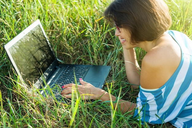 Adult beautiful woman using laptop in nature