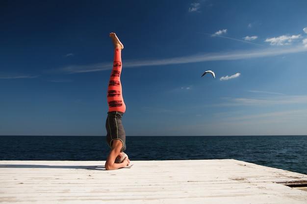 Взрослая белокурая женщина с короткой стрижкой занимается йогой на пирсе на фоне моря и голубого неба