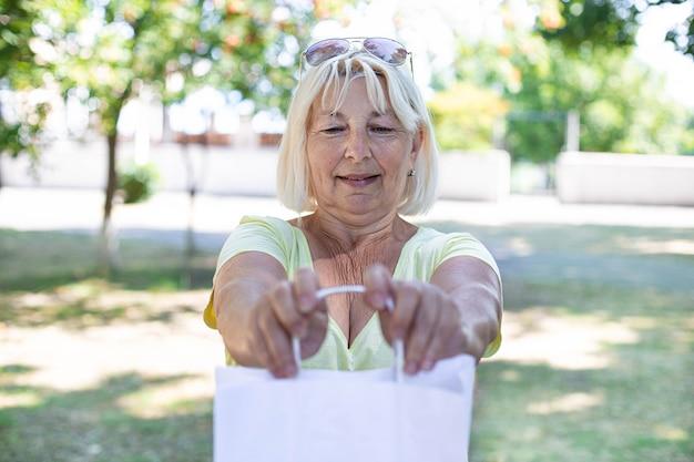 通りに立っている白い紙袋を持つ大人のブロンドの女性ショッピングコンセプト