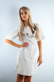 白い医療用ガウンの大人の金髪の美しい看護師