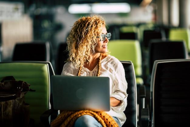 大人の金髪の巻き毛の女性は、空港の待合室に一人で座っているラップトップコンピューターで働いています-テクノロジーとインターネットを使ったスマートなリモートワーカー活動の旅行と現代人