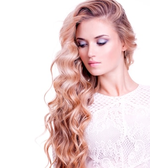 Adult blonde girl with long blond curly hair. portrait of a pretty woman  over white wall.