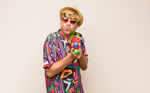 Взрослый блондин в праздники, держа в руках водяной пистолет.