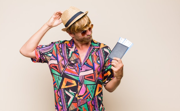 Adult blonde man with a passport and boarding plane tickets