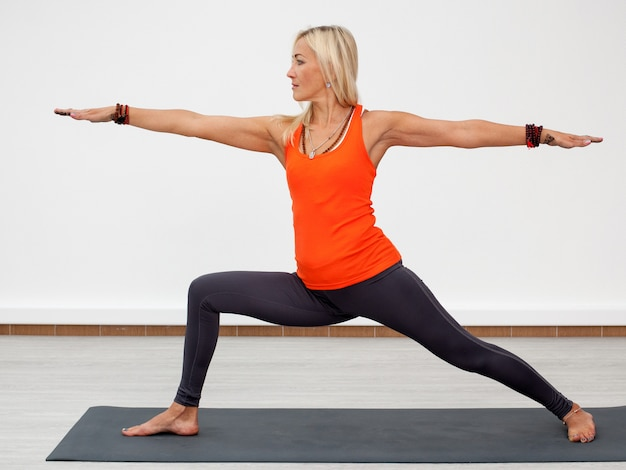 Adult blonde woman doing warrior pose on mat