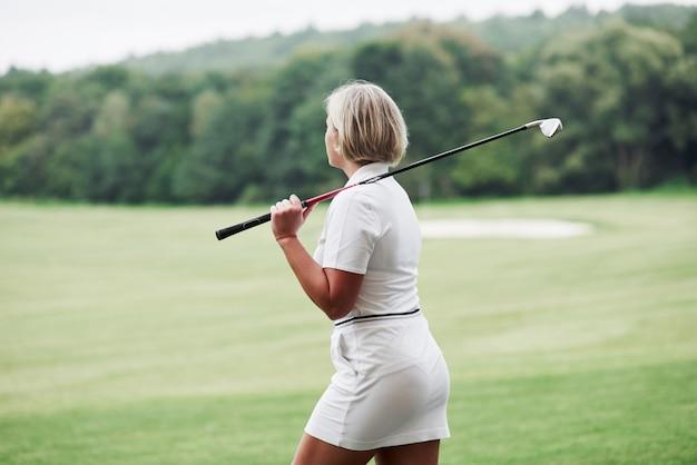 성인 금발 여자는 골프 스틱을 잡고 필드에 산책을했습니다.