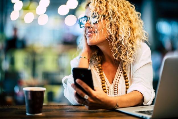 大人の金髪の女性は笑顔で、電話とラップトップコンピューターでうめき声とインターネット技術を使って作業します-焦点がぼけたボケ色の背景を持つオフィスのデスクトップワークステーション