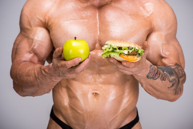 Adult bodybuilder is holding apple in his hand.