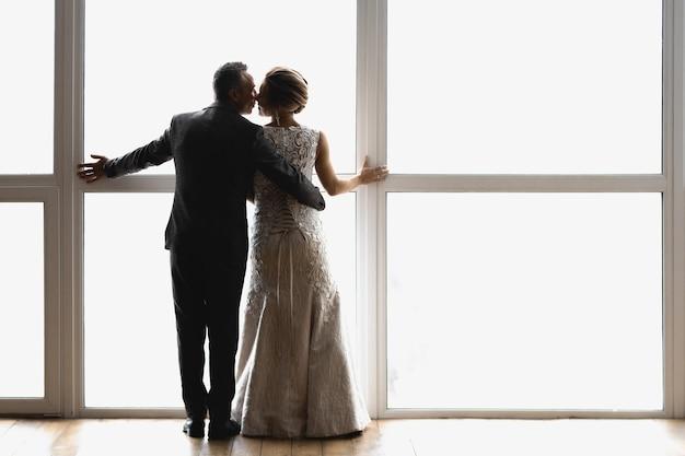 Взрослые жених и невеста обнимаются и встают у большого окна спиной к зрителю