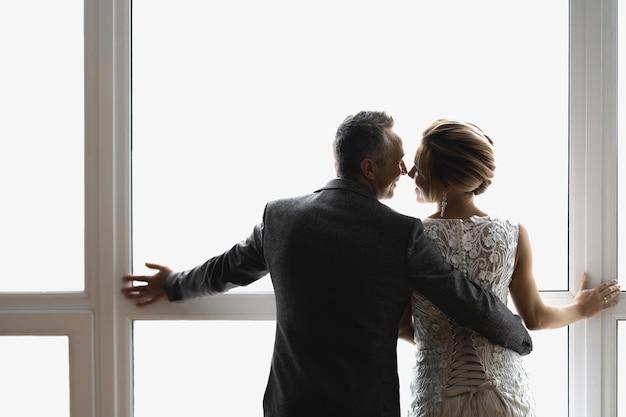 大人の新郎新婦が抱きしめ、大きな窓の近くに立って、見る人に背を向けます