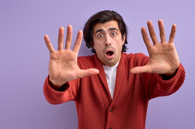 Adult brunette man over isolated background doing stop gesture with fear expression.