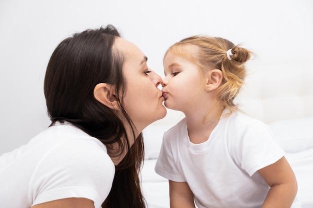 彼女の小さな金髪の娘にキスする大人のブルネットの母親