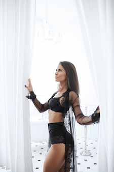 Donna castana adulta in biancheria nera sexy
