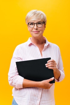 Adult business woman in eyeglasses looks into camera and holds paper tablet
