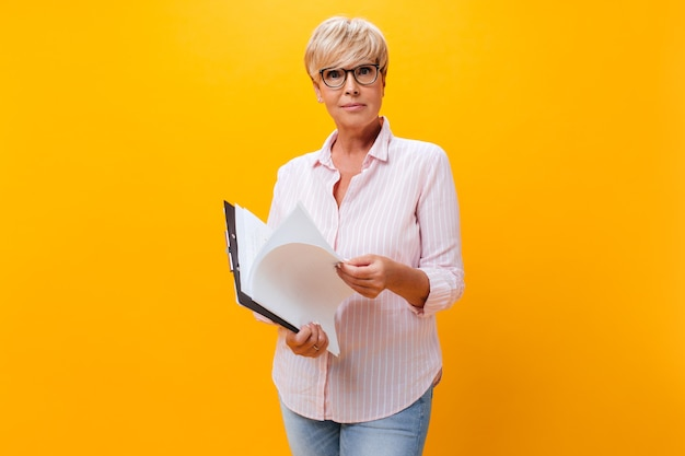 Adult business woman holds tablet with paper sheets