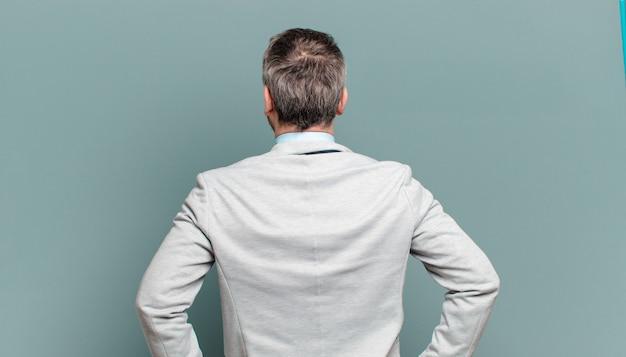 大人のビジネスマンが混乱したり、満腹になったり、疑問や質問を感じたり、疑問に思ったり、腰に手を当てたり、背面図