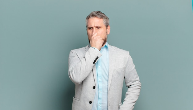 Adult businessman feeling disgusted, holding nose to avoid smelling a foul and unpleasant stench