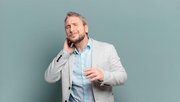 Взрослый бизнесмен чувствует стресс, разочарование и усталость, потирая болезненную шею, с встревоженным и встревоженным взглядом