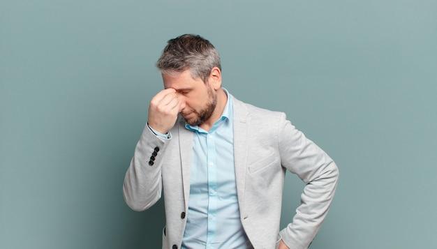 Взрослый бизнесмен чувствует себя напряженным, несчастным и разочарованным, касается лба и страдает от сильной мигрени