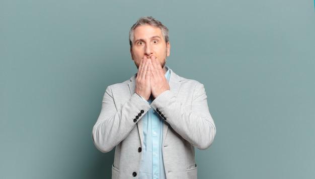 Взрослый бизнесмен чувствует себя обеспокоенным, расстроенным и напуганным, прикрывает рот руками, выглядит встревоженным и испорченным