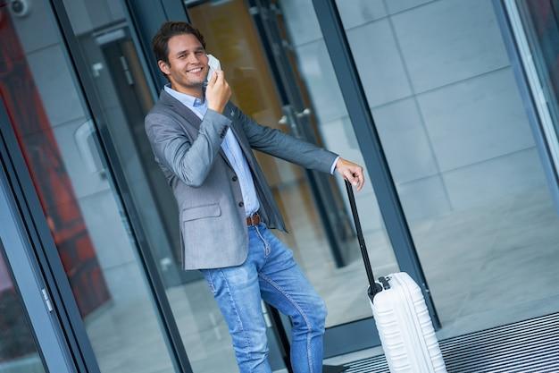 Взрослый бизнесмен покидает отель в маске из-за ограничений, связанных с covid-19