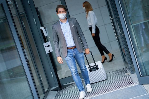 Adult businessman leaving hotel in mask due to covid-19 restrictions