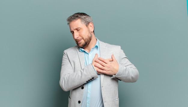 Взрослый бизнесмен выглядит грустным, обиженным и убитым горем, держит обе руки близко к сердцу, плачет и чувствует себя подавленным