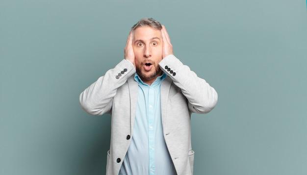 Взрослый бизнесмен выглядит неприятно шокированным, напуганным или обеспокоенным, с широко открытым ртом и закрывающим оба уха руками