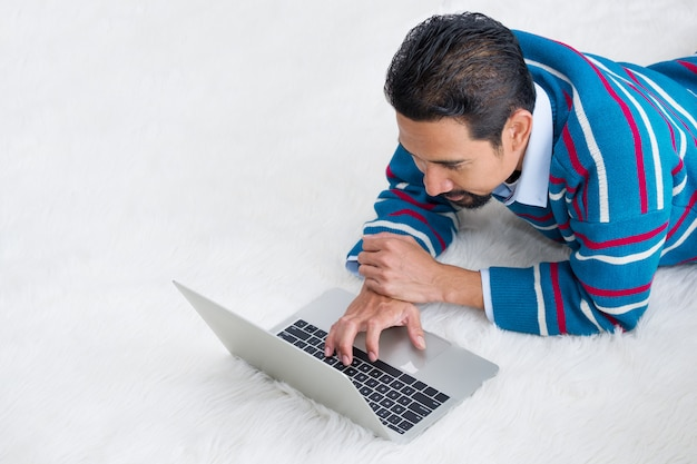Adult businessman lying on the wool rug with a laptop.