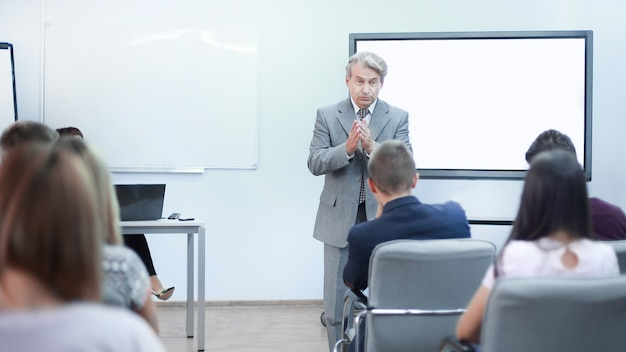 Adult businessman makes a report for employees at a meeting in the office.
