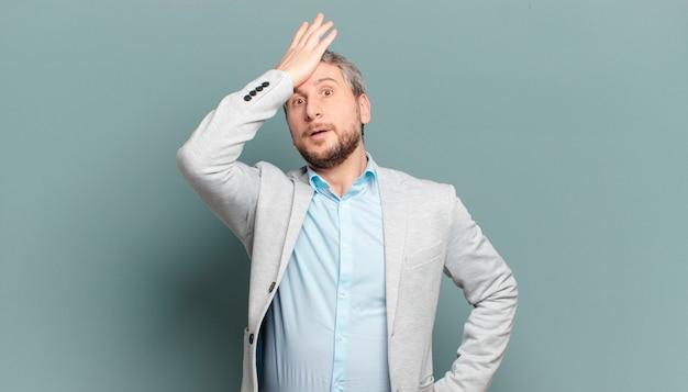 愚かな間違いをした後、または思い出した後、おでこを考えて手のひらを上げる大人のビジネスマンは、愚かさを感じます