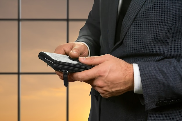 Adult businessman's hands holding wallet. wallet on sunny sky background. safety above all. hope it's not empty.