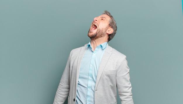 Взрослый бизнесмен яростно кричит, агрессивно кричит, выглядит напряженным и злым