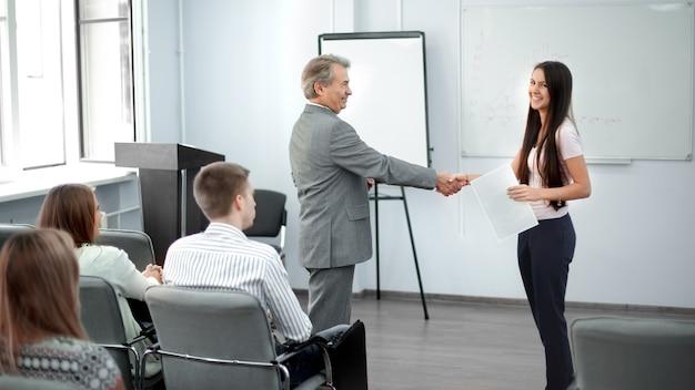 会社の若い従業員と握手する大人のビジネスマン。