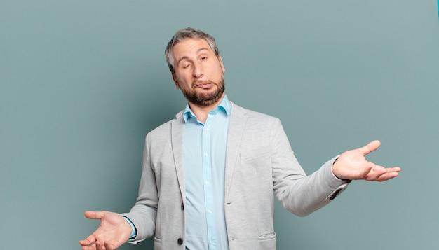 Взрослый бизнесмен пожимает плечами с глупым, сумасшедшим, растерянным, озадаченным выражением лица, чувствуя раздражение и невежество