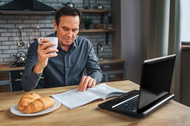 Adult businessman sit at table in kitchen anr read journal. he hold white cup and look down. laptop and plate with croissans on table.
