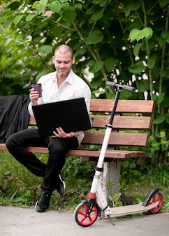 Uomo d'affari adulto che si siede su un banco all'aperto