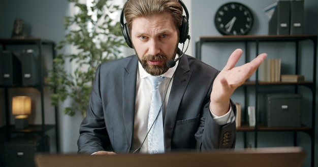 Adult businessman sitting at computer with headset on using it to talk to client or partner and gesturing