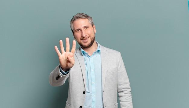 Взрослый бизнесмен улыбается и выглядит дружелюбно, показывает номер четыре или четвертый с рукой вперед, считает