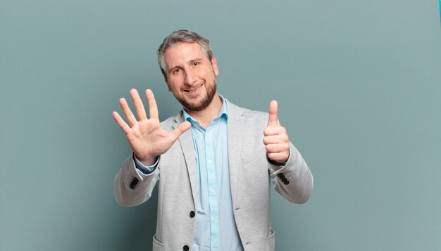 Взрослый бизнесмен улыбается и выглядит дружелюбно, показывает номер шесть или шестой рукой вперед, отсчитывая