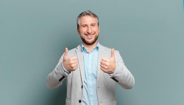 Взрослый бизнесмен, широко улыбаясь, выглядит счастливым, позитивным, уверенным и успешным, с двумя пальцами вверх
