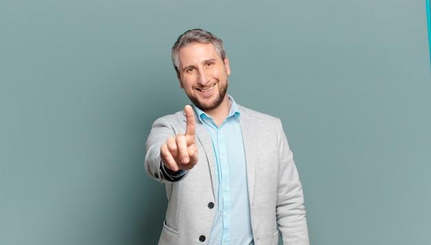 Взрослый бизнесмен, гордо и уверенно улыбаясь, триумфально принимает позу номер один, чувствуя себя лидером