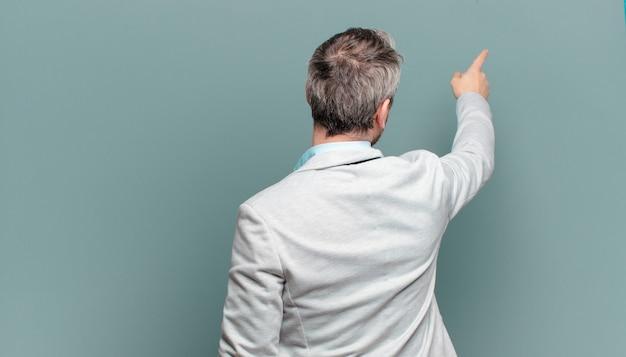 Взрослый бизнесмен стоял и указывая на объект на копировальном пространстве, вид сзади