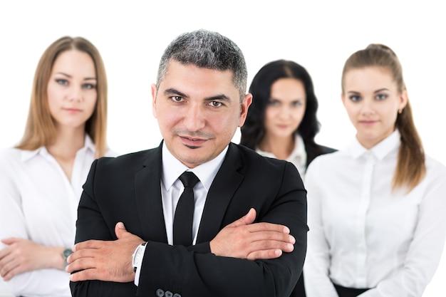 腕を胸に組んで同僚の前に立っている大人のビジネスマン。ビジネス人々チームのグループ