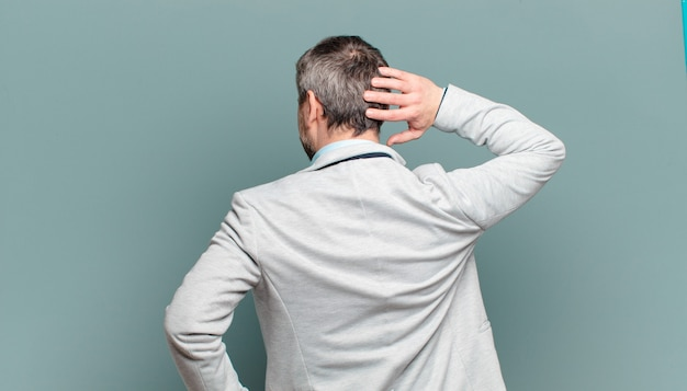 성인 사업가가 생각하거나 의심하고, 머리를 긁적이며, 어리둥절하고 혼란스러워하며, 뒷모습이나 뒷모습