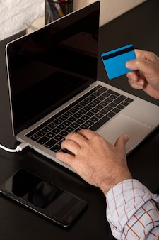Adult businessman using a credit card and using laptop making an online purchase from home. online shopping